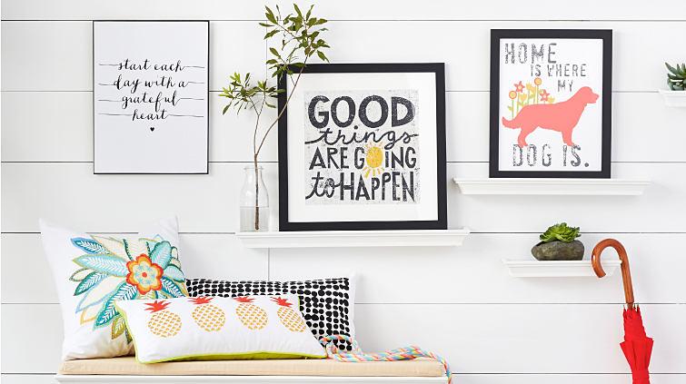 An assortment of framed wall art and decorative throw pillows.