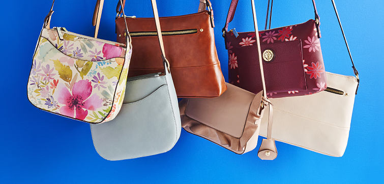An assortment of shoulder handbags in different colors and prints.