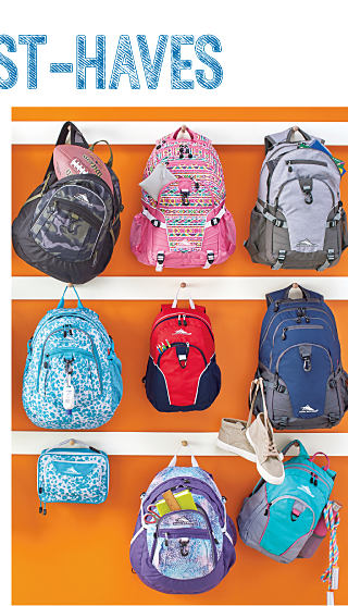 An assortment of backpacks hanging from hooks on an orange wall.
