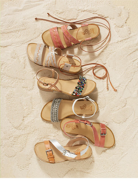 An assortment of women's sandals in the sand.