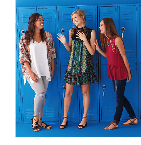 Three young women wearing various young contemporary styles standing in front of a wall of blue lockers.
