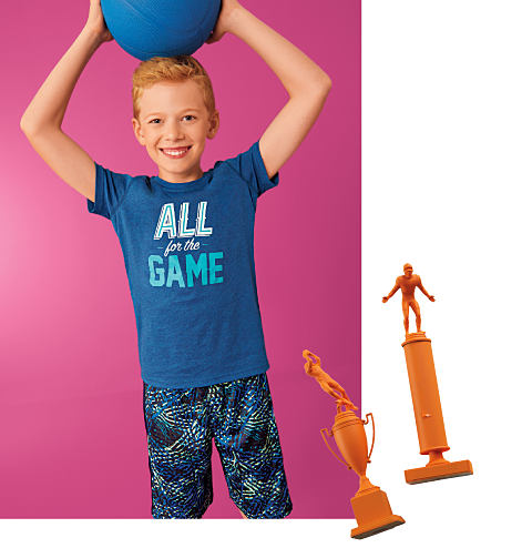 "A boy wearing a blue ""All for the Game"" graphic print T-shirt and multi colored print shorts."