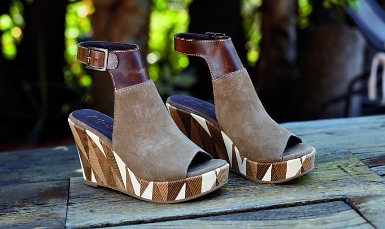 A pair of suede and leather wedges with a decorative heel.