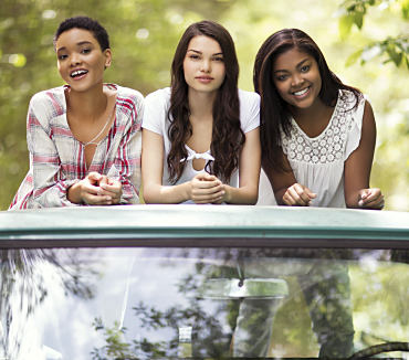 Three young women standing in the back of a pickup truck wearing casual clothing from True Craft.