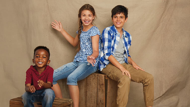 Three children sitting together wearing casual clothing from True Craft.