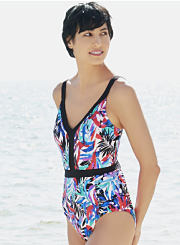 A woman wearing a printed one-piece swimsuit while walking on the beach. Shop swimwear.