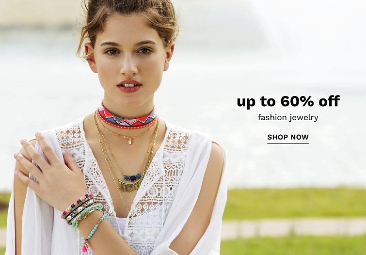A young woman wearing an assortment of layered necklaces and bracelets. Up to 60% off Fashion Jewelry.