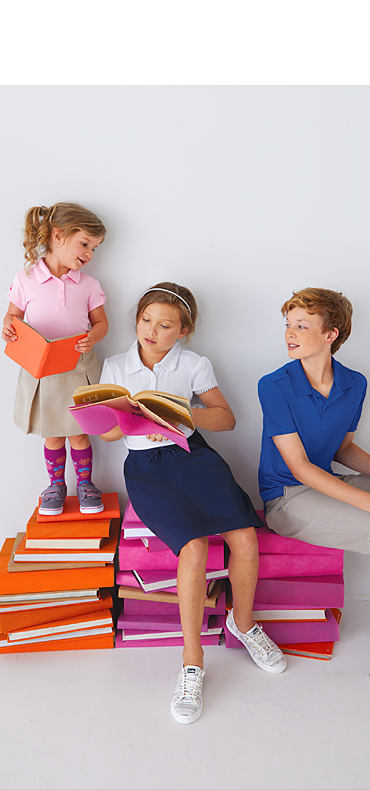Two girls and a boy wearing various styles of school uniforms sitting on stacks of books.