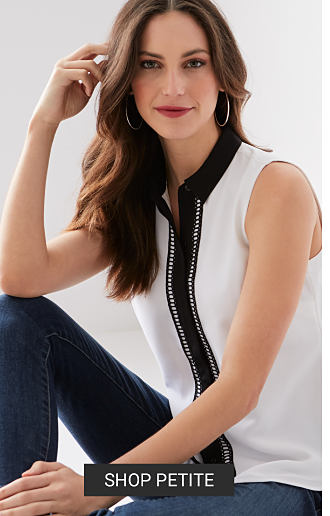 A woman in a black and white sleeveless blouse and jeans. Shop petite.