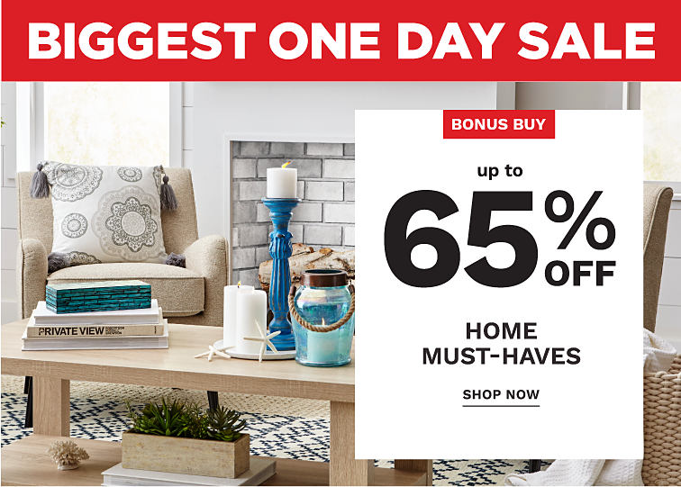Biggest One Day Sale. Up to sixty five percent off home must-haves. A living room with an area rug, throw pillows on chairs and candles on a coffee table.