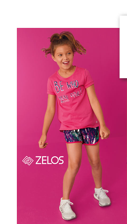 A girl wearing a pink Zelos graphic T shirt and multi colored gym shorts with white sneakers.