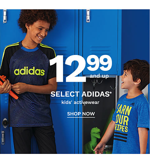 Two boys wearing various styles of Adidas active wear in front of a wall of blue lockers.