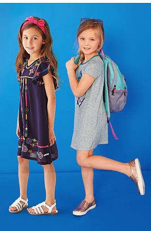 A girl wearing a blue short sleeved dress with a multi colored print on it, standing next to a girl wearing a gray short sleeved dress.