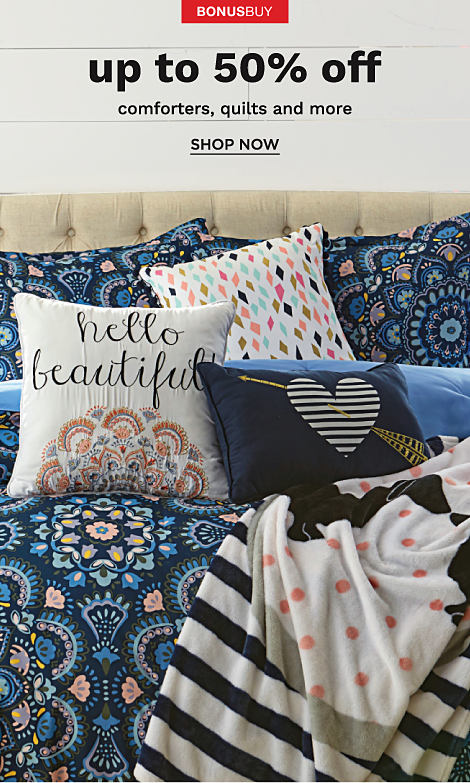 A bed made with a multi colored print comforter and an assortment of novelty throw pillows.