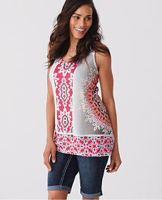 A woman wearing a pink and white patterned sleeveless top and blue jeans.