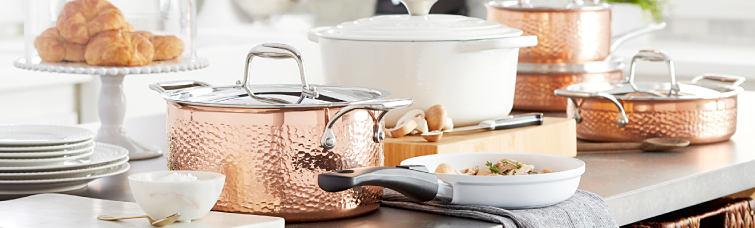 An assortment of copper pots & pans, white enamel pots & skillets & white dishes. Kitchen Essentials.