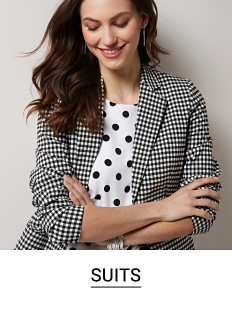 A woman in a black and white polka dot top and a gingham blazer. Shop suits.