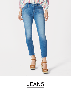 A woman in jeans and wedges. Shop jeans.