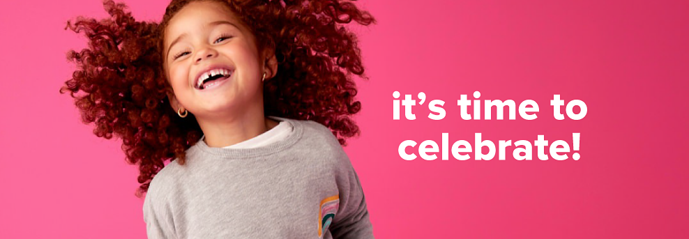 A little girl laughing wearing a grey long sleeve shirt with a small graphic on the chest. It's time to celebrate!