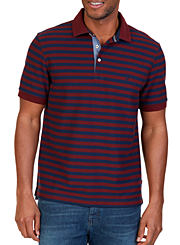 A man wearing a blue and red striped polo and blue jeans. Shop polos.