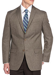 A man wearing a brown sportcoat, white shirt, blue and white tie and black pants. Shop suits and sportcoats.