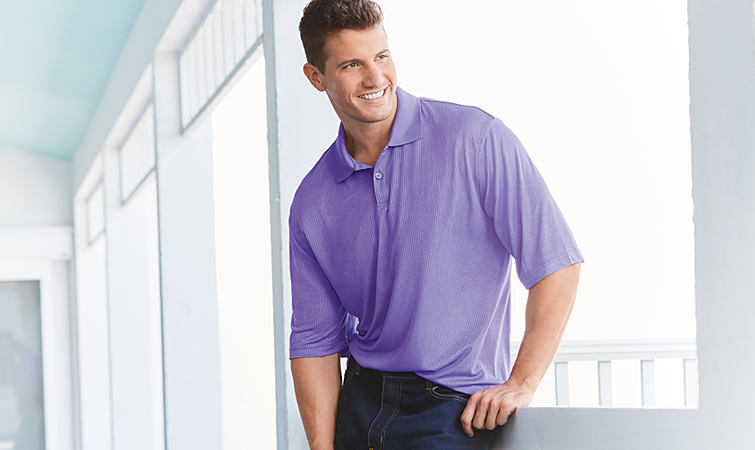 A man wearing a purple polo and blue jeans.