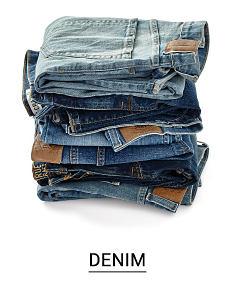 A stack of folded denim pants. Shop denim.