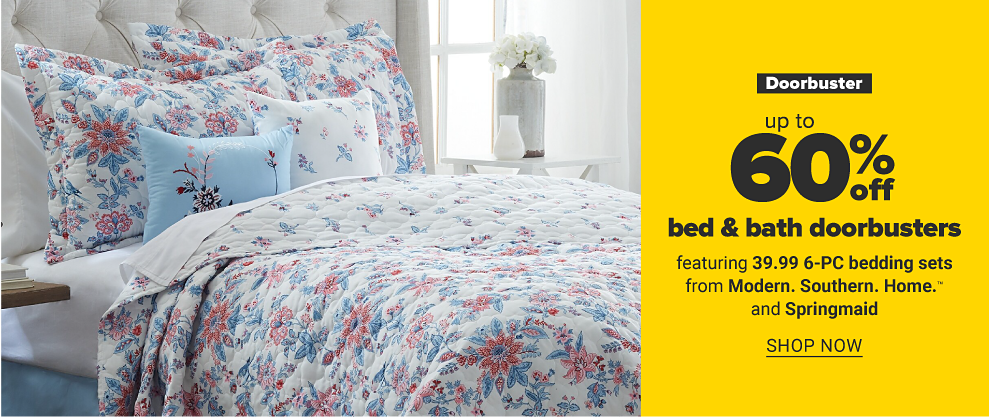 A floral bedset featuring red flowers and blue leaves against a white comforter, with matching pillows. Doorbuster up to 60 percent off bed and bath doorbusters featuring 39.99 six-piece bedding sets from Modern Southern Home and Springmaid. Shop now.