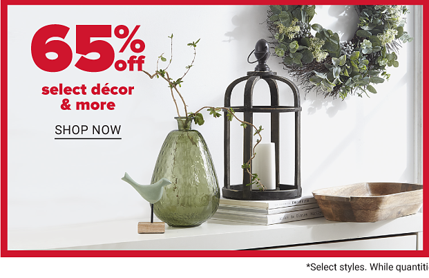 A shelf featuring home decor: a wreath, candle holder, a green vase, a small bird and a wood tray. 60 percent off select decor and more. Shop now.