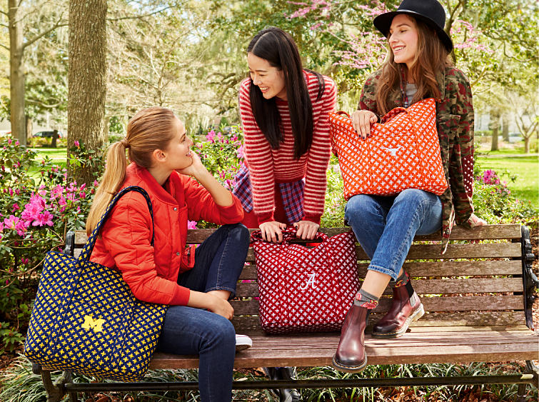 Young women on a college campus with printed collegiate bags from Vera Bradley.
