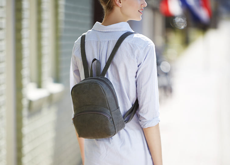 A woman wearing a mini fashion backpack.