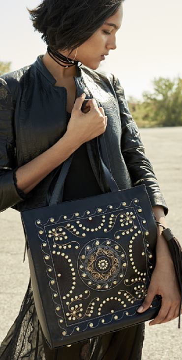 A woman holding a leather tote with embellished details.
