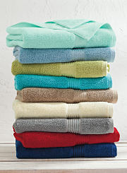 A Stack of bath towels in a variety of colors. Shop towels.