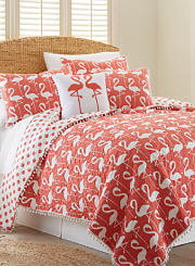 A bed made with a salmon and white flamingo patterned quilt and matching pillows. Shop quilts.