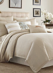 A bed made with a beige comforter and matching pillows. Shop comforters.