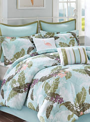 A bed made with a blue, white, green and purple tropical patterned comforter and matching pillows. Shop bed in a bag.
