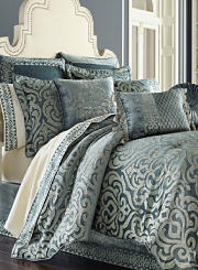 A bed made with a gray and green paisley comforter and matching pillows. Shop bedding collections.