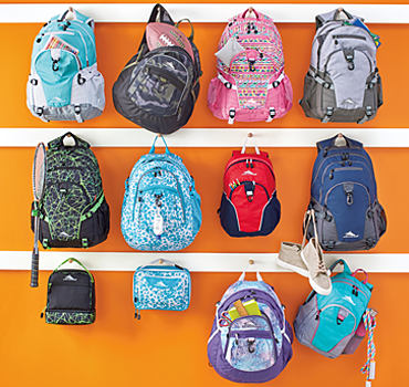An assortment of kids' backpacks in a a variety of colors and patterns.