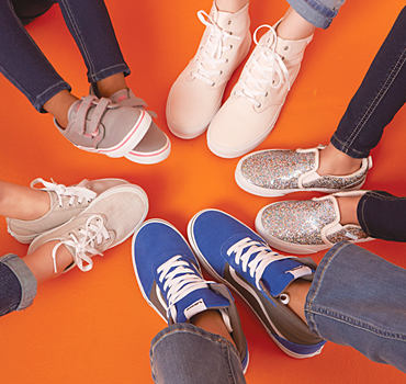 Five kids wearing various colors and styles of sneakers, making a circle with their feet.