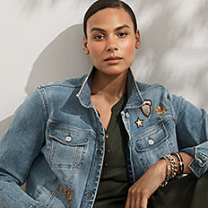 A woman wearing a denim jacket over an olive green top. Shop women's plus.
