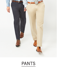 Two men walking, one wearing navy pants and light brown shoes and the other in khaki pants and light brown shoes. Shop pants.