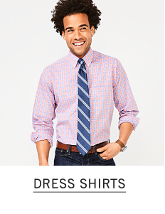 A man in a pink dress shirt and blue and white stripe tie. Shop dress shirts.