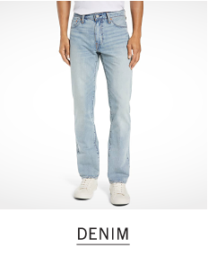 A man in light blue jeans and white sneakers. Shop denim.