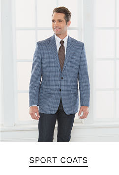 A man wearing a gray sport coat, a white dress shirt, a brown tie & blue jeans. Shop sport coats.