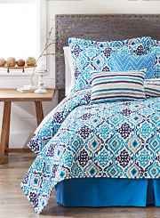 A bed made with a printed comforter and matching pillows in various shades of blue, gray and white. Shop Bed in a Bag.