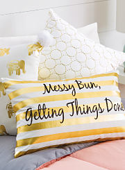 "A bed with multiple throw pillows including one with a graphic that reads ""Messy Bun, Getting Things Done."" Shop throw pillows."