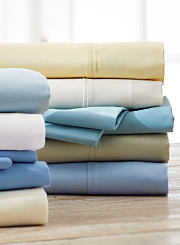An assortment of bed sheets in blue, white, yellow and green. Shop sheets.