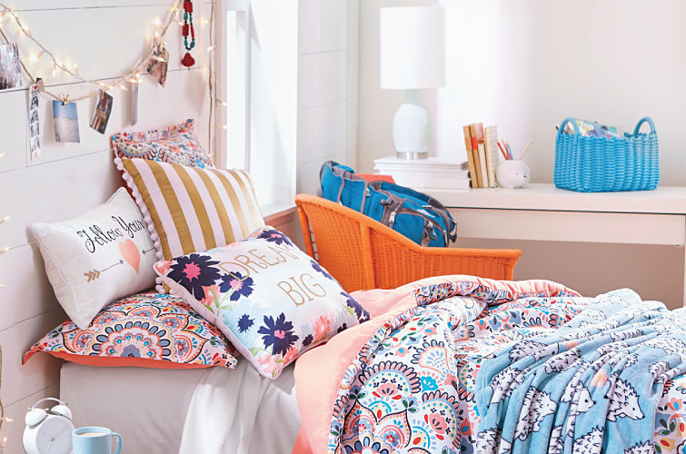 A dorm room decorated with a colorful print comforter, string lights and pops of orange and blue accents.