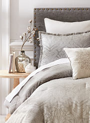 A bed with a decorative comforter and neutral-colored furniture. Shop comforters.