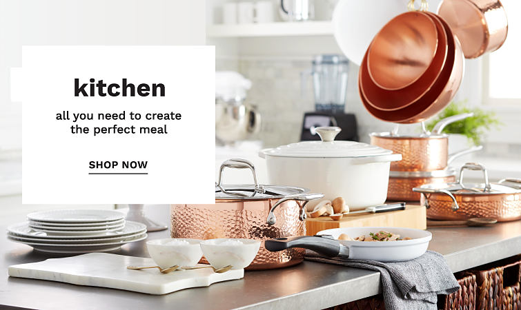 A kitchen island with copper pots, pans and bowls and an assortment of serving dishes.
